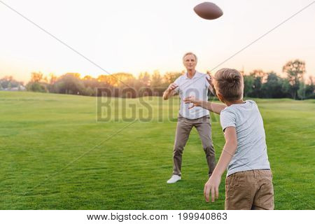 Grandfather And Grandson Playing Rugby