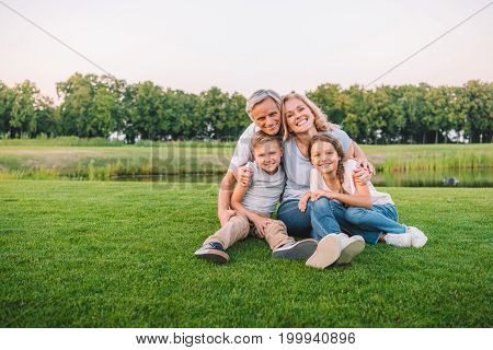 Family Resting On Meadow