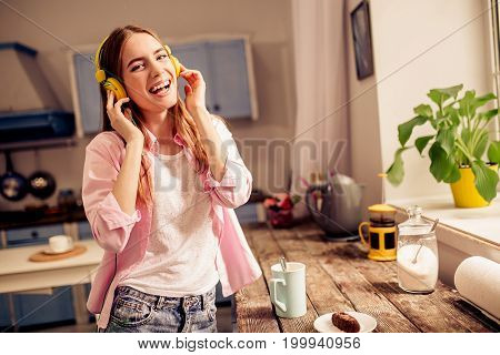 Happy girl in headphones smiling listening music at home. Female in the kitchen standing close to wooden desk drinking tea enjoying music.