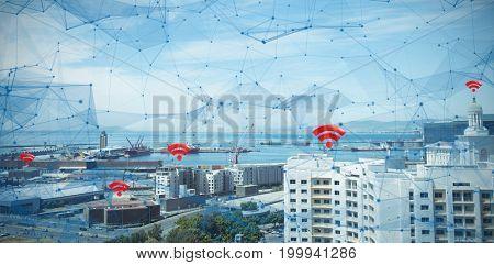 Red wifi symbol against buildings by sea against sky