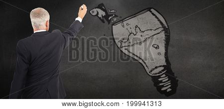 Rear view of serious businessman standing and writing against black wall