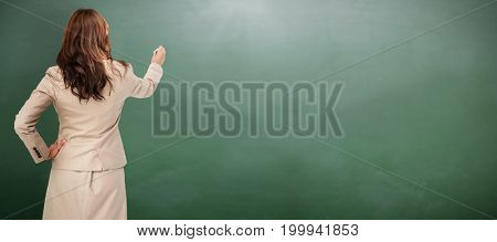 Businesswoman standing back to camera writing with marker against green chalkboard