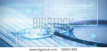 Digital image of brain with DNA helix and graph against close-up of keyboard with stethoscope
