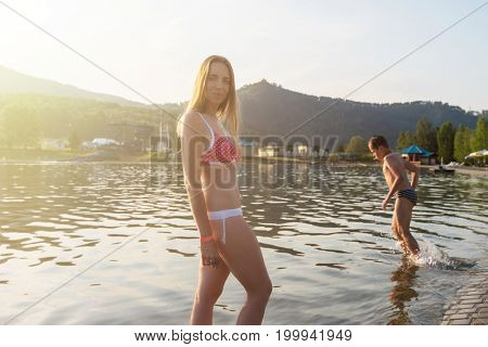 Woman at aquapark and her son playing in the water