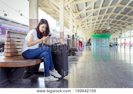 Young girl asian backpack travel using smartphone mobile with carrying hold suitcase luggage booking ticket in train station railway platform way vacation time in holiday relaxation.