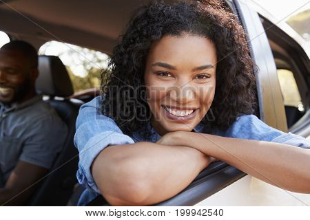 Young black woman looking out of car window smiles to camera