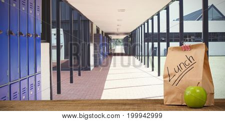 Lunch bag with apple on wooden table  against empty corridor at school