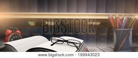 School supplies on desk against volumes of blue books on bookshelf