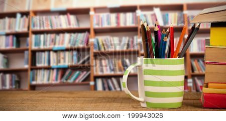 Stack of books by mug with colored pencils on wooden table against low angle view of various books on shelf