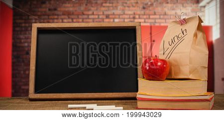 Slate with chalks by lunch bag and books on wooden table against orange lockers against brick wall