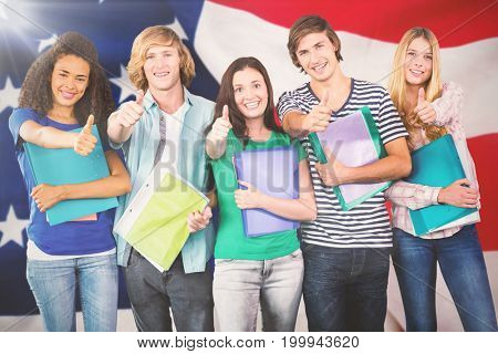 Happy college students gesturing thumbs up against close-up of flag