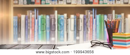 School supplies on desk against multi colored books on shelf in library