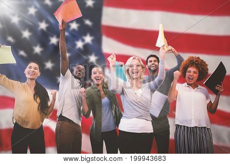 Cheerful business people holding files against close-up of an flag