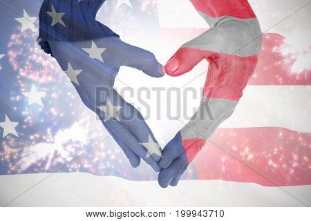 Close up of hands forming heart against close-up of us flag