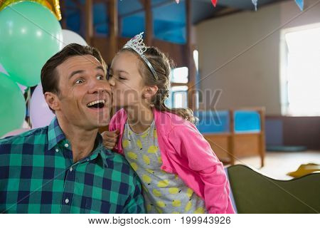 Smiling daughter kissing his father at home