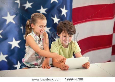 Boy with sister using digital tablet against flag with stripes and stars