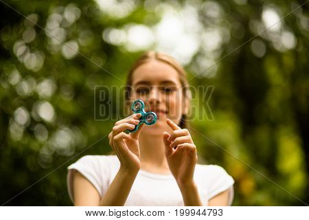 Beautiful young girl outdoors playing with fidget spinner. Summer day female relaxing in park holding spinner.