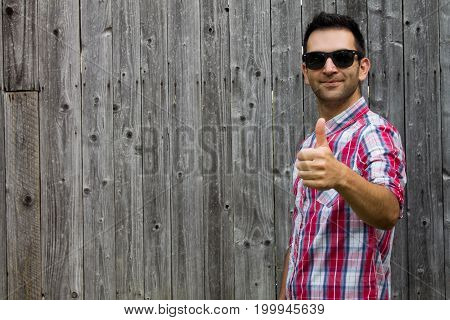 Portrait of man giving thumbs up sign wearing sunglasses smiling while standing against wooden background.