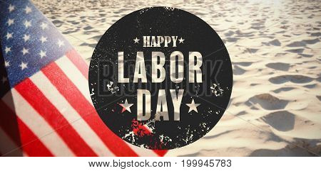 Digital composite image of happy labor day text poster against surface of rippled sand