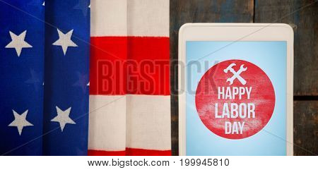 Flare against digital tablet by american flag on table