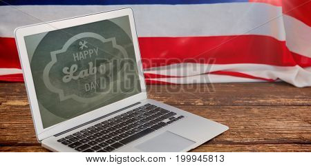 Blurry animated flare against laptop and american flag on wooden table