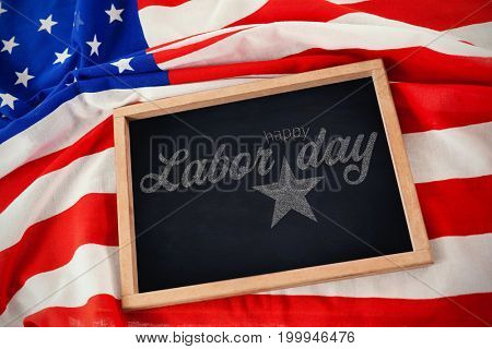 Digital composite image of happy labor day text with star shape against american flag with chalkboard
