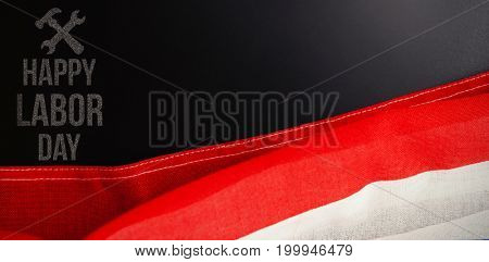 Digital composite image of happy labor day text with tools against american flag and empty slate on wooden table