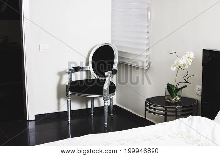 Image Of A Bedroom In A Classical Interior With A Black Chair.