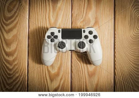 video game controller on a wooden table. joystick