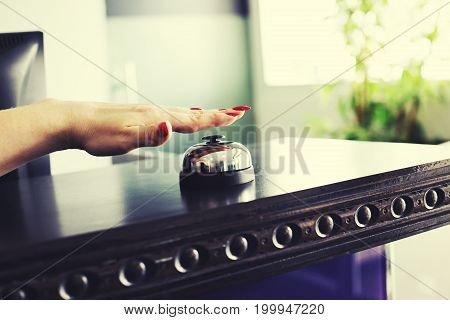 Close up of woman hand ringing bell at hotel at reception desk. Closeup of female hand ringing service bell.