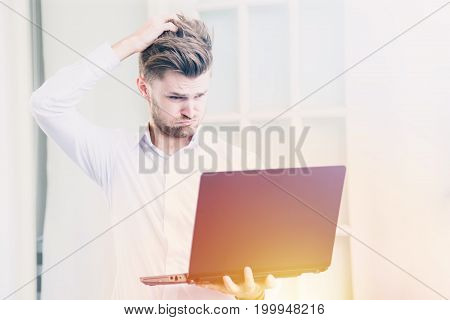 Young businessman looking laptop notebook with shocked negative stress posture in office , warm tone filter