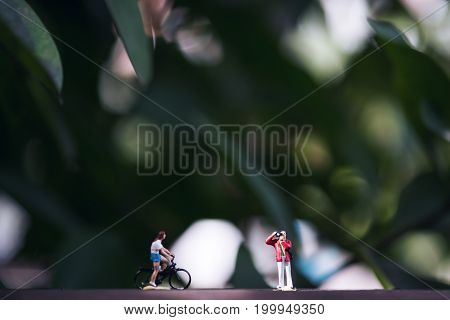 Closeup image of small photographer and bicycle rider model figures on wooden floor with blur green nature background