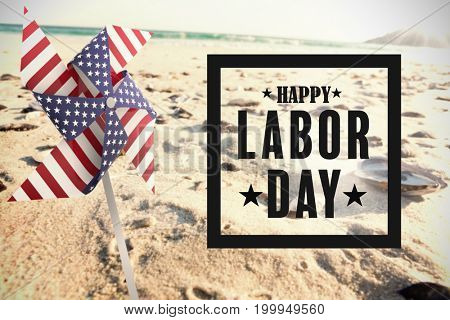 Composite image of happy labor day poster against sea shells on sand surface