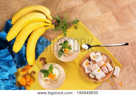 A view from above on a bright composition of ripe bananas, fruit ice cream in dessert glasses, Turkish Delight on a wooden plate, dried apricots, walnuts, and mint leaves on a wooden background..