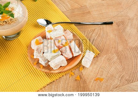 A heap of fantastic turkish delight on a ceramic plate on a light brown wooden table background. Rahat lokum with fruits, sugar powder and a drink. An exotic dessert with long metal spoon.