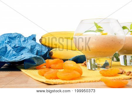 A close-up picture of dessert glass filled with thick banana dessert isolated on a white background. Tropical smoothie with decorative mint leaves and dried apricots on a bright yellow cloth.