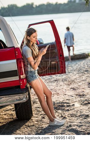 beautiful young woman in earphones listening music with smartphone while leaning on car at riverside
