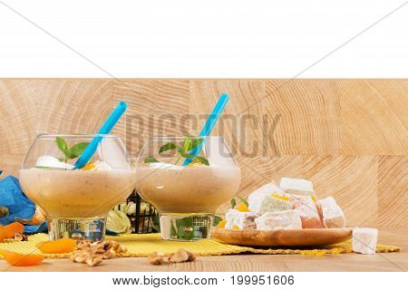 Two banana milkshakes with mint and apricots in big glasses isolated on a white background. A colorful set of powdered turkish delight, walnuts and aromatic mint next to smoothies on a wooden desk.