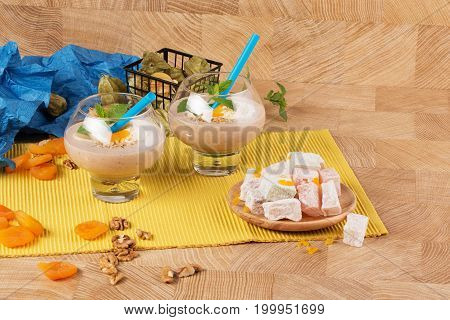 A pair of milkshakes with vanilla ice cream, apricots, mint and blue straws on a wooden background. Beautiful composition of natural desserts and products: turkish delight, physalis fruits, walnuts.