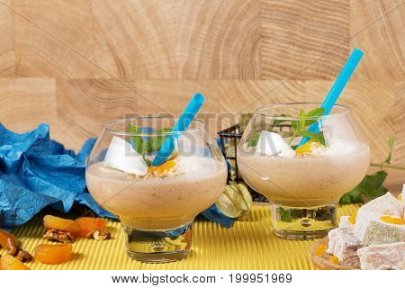 A plate of lokum, rahat lokum, glasses of cocktails, decorated with mint leaves, dried apricots, physalis, walnuts on a blurred colorful background.