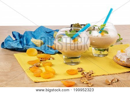Fruity smoothies in dessert glasses isolated on a white background. A beautiful composition of two dessert glasses filled with thick ice cream with bright blue straws on a light wooden table.
