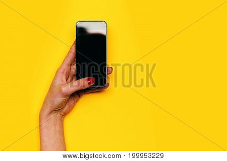 communication and technology girl touch mobile or cell phone screen with hand has red manicure on yellow background. internet surfing video conferencing copy space