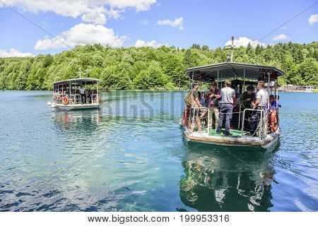 CROATIA PLITVICE, 29 JUNE 2017: Groups of tourists on boats cruising along the Plitvice Lakes.