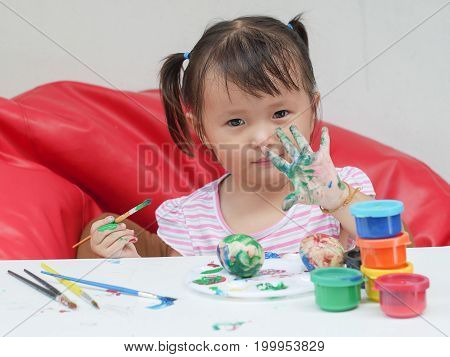 Little Girl Painting with paintbrush and colorful paints .children development concept.