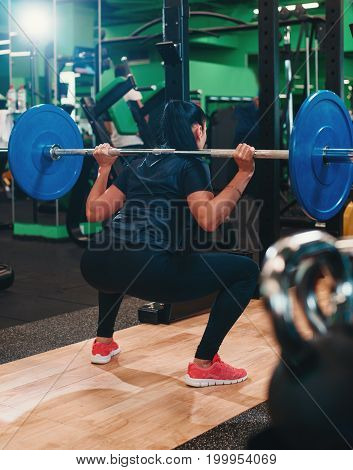 Young woman exercising in gym doing squats with Olympic barbell