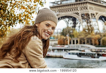 Smiling Young Tourist Woman On Embankment In Paris, France