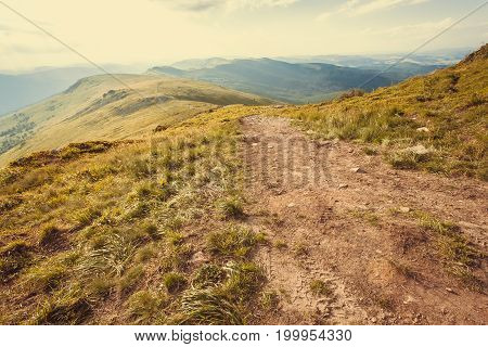 Mountain range and dirt roan on top. Nature landscape with rural way in grass. Beautiful scenery in the Carpathian Mountains.