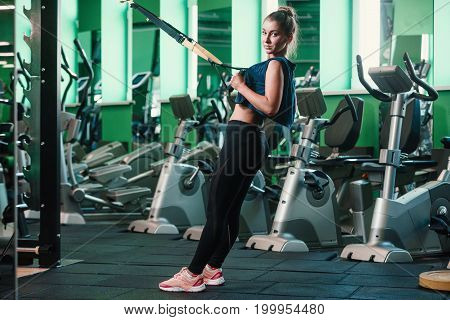 Beautiful athletic woman doing exercise with trx system. Young woman exercising with suspension trainer at gym.