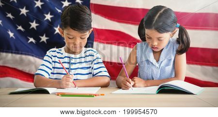 Children writing on books at table against close-up of an flag
