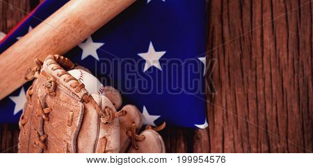 Close-up of baseball bat and gloves on American flag